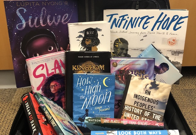 An assortment of books for young readers from 2019 arranged in a suitcase