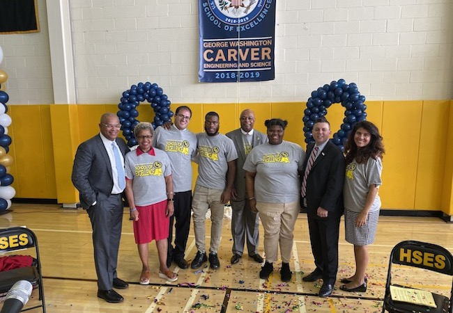 School leaders at Carver High School pose in front of Blue Ribbon banner