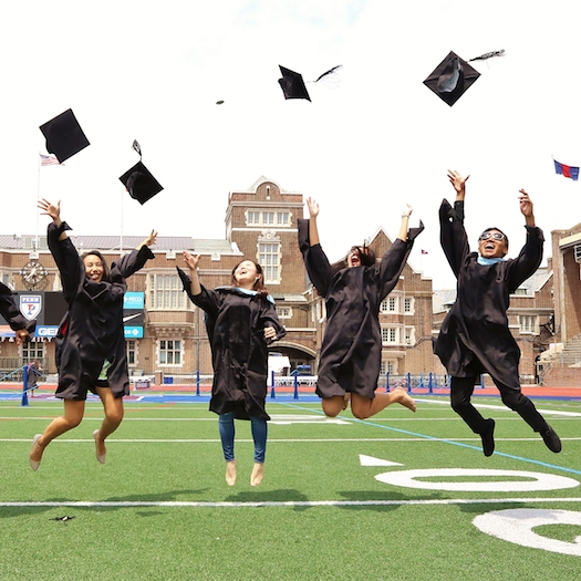 Four Penn GSE graduates jumping in the air as they throw their caps.
