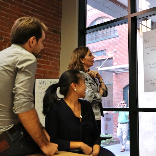 Two women and one man looking intently at chart taped to a window.
