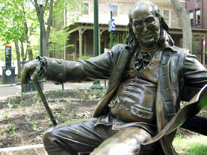Statue of Benjamin Franklin sitting on a bench