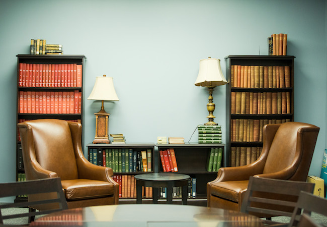 A boardroom with two empty large leather chairs in front of bookcases.
