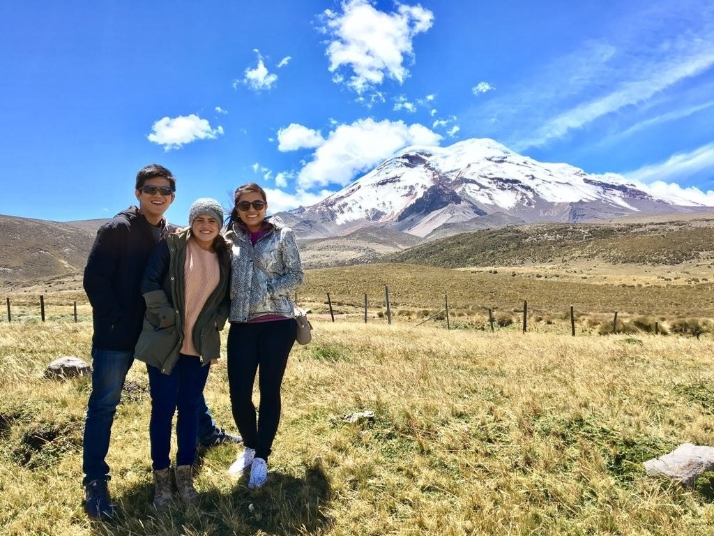 Trio posing with mountain in background.
