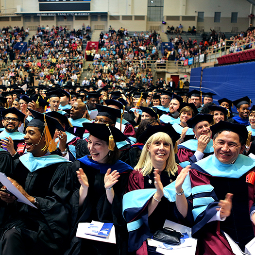 Graduate students in caps and gowns sitting and clapping