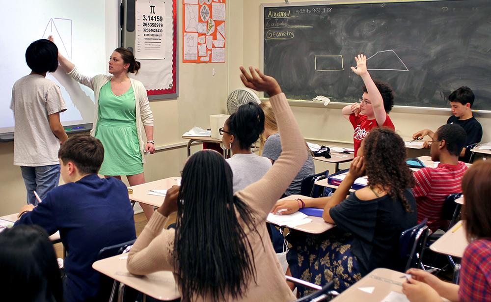 Students in class, two raising their hands.