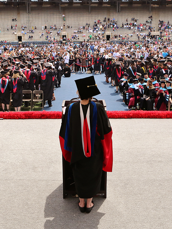 Woman in cap and gown standing on stage facing crowd of students in caps and gowns