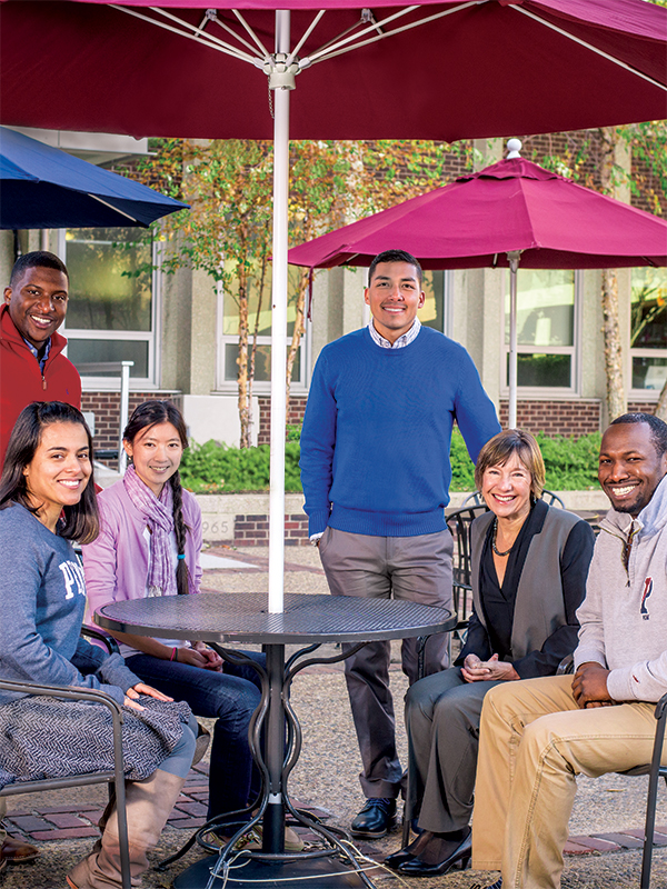 Dean and students around table outdoors in Penn GSE courtyard