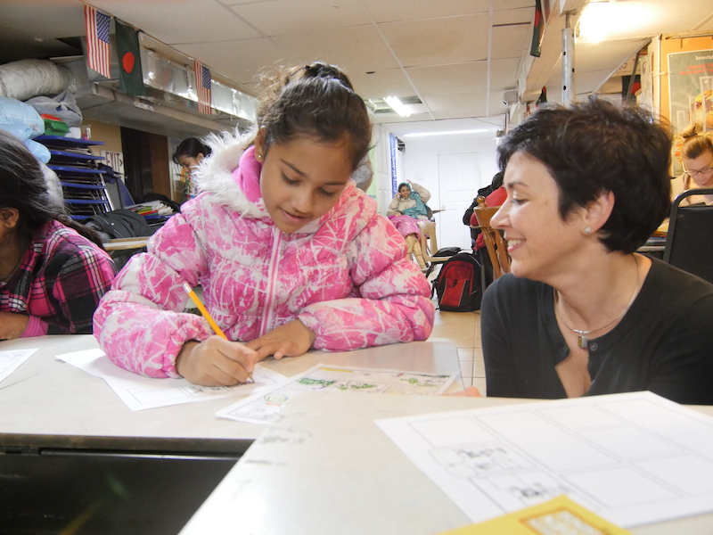 A child in the Bangladeshi after school program Moder Patshala sits at a table, drawing a graphic novel page, while Anne Pomerantz kneels next to her