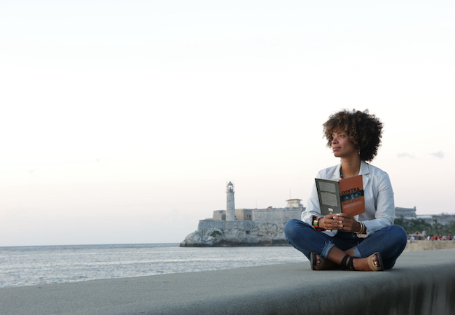 Amalia Dache sits on a ledge overlooking a harbor during a research trip to Cuba.