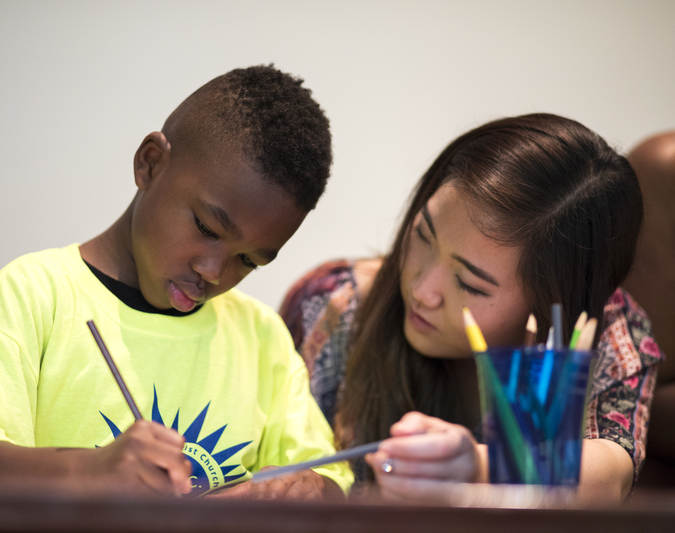 A student teacher draws with a young child in a summer enrichment program