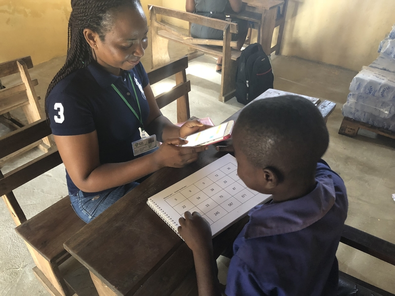 A teacher works with a student in Ghana.