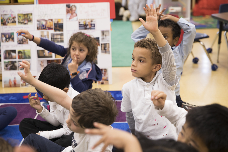 A boy raises his hand in a kindergarten class.