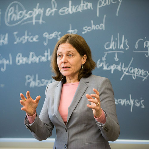 A professor addresses a class, standing in front of a blackboard with white chalk writings related to philosophy and education.