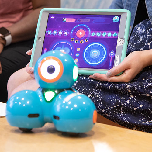 A blue robotic device with three spheres sits on a table. Behind it, an individual holds up a tablet device showing illuminated circles.