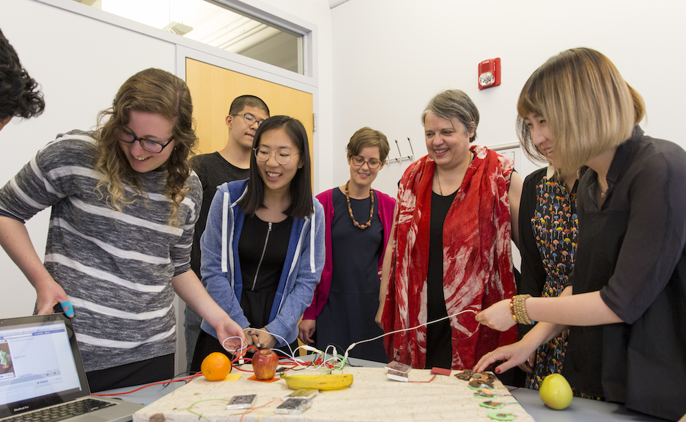 Professor and students smiling as they connect electronic sensors to fruits and other objects