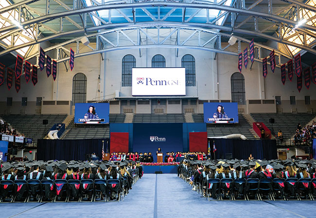 "Inside Penn's Palestra, graduates in caps and gowns are seated in rows facing the stage, where faculty are similarly dressed and seated and a speaker stands at a podium. Above the podium, a large screen reads ""Penn GSE."""
