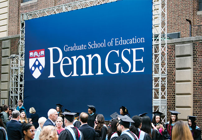 Penn GSE graduates in regalia and their family and friends gather in front of a large, blue sign with the Penn GSE logo.]