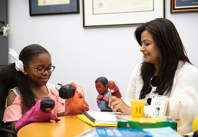 An elementary school student sitting at a table in an office looks down at two puppets held in her hands, and across from her is a smiling woman holding two other puppets. A notebook and folders are on the table.
