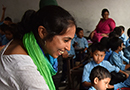 A smiling woman interacting with a class of Nepalese students