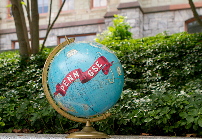 A globe with a banner that says Penn GSE is sitting outdoors next to green hedges