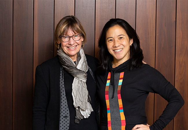 Dean Pam Grossman and Angela Duckworth stand in front of a wood paneled wall smiling at the camera