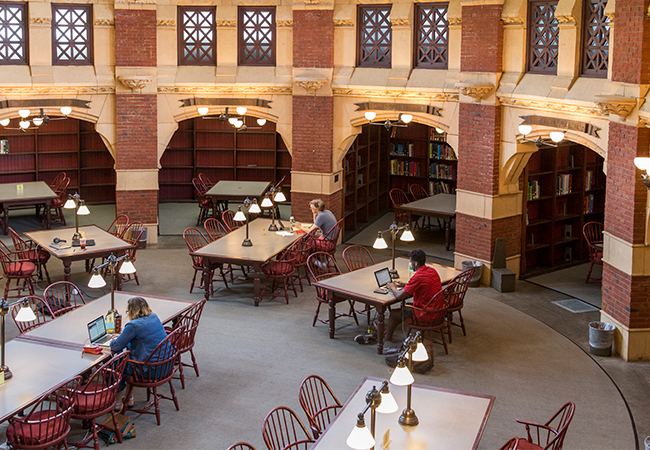 Aerial shot of three people sitting at separate tables in a library, working on laptops