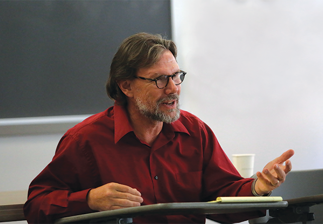 Photo of Michael Nakkula in a red button-up shirt and glasses sitting at a desk and teaching