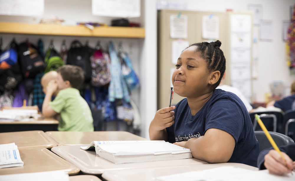 Philadelphia middle school student at a classroom desk tapping a pencil on her chin