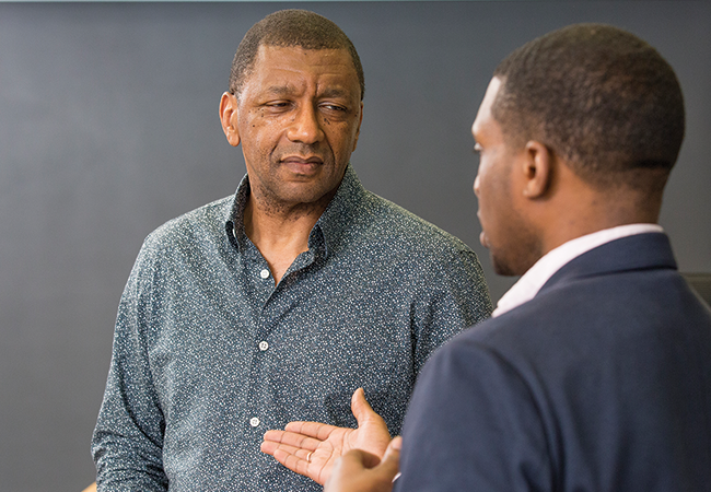Dr. Stevenson stands in front of a chalkboard conversing with a student.
