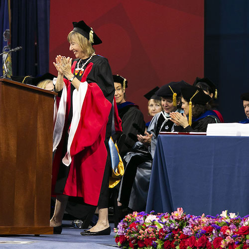 Penn GSE's dean and faculty are onstage wearing graduation caps and gowns, applauding with smiles on their faces during a commencement ceremony.
