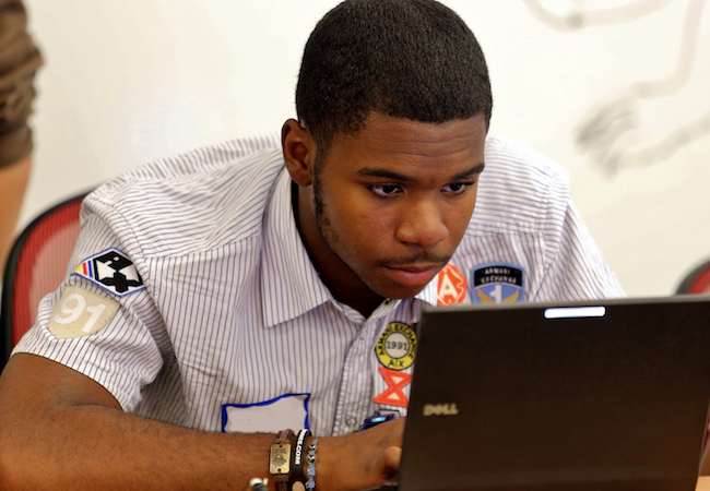A student sits and works at a laptop computer.