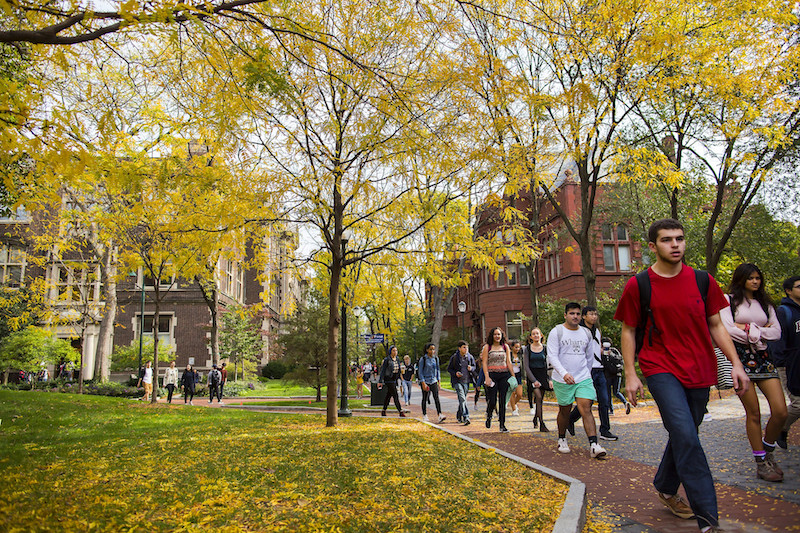 Penn students walk along a campus pathway among the autumn colors.