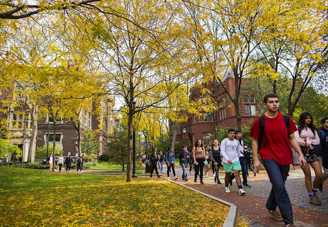 Students walk across a college campus in the fall.