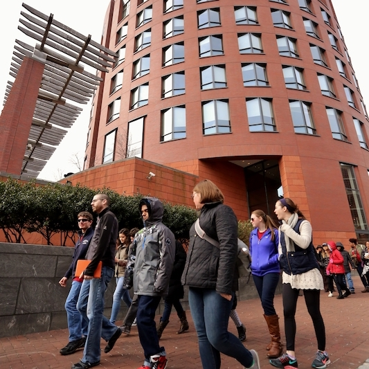 A group of students walks in front of Wharton's Huntsman Hall.