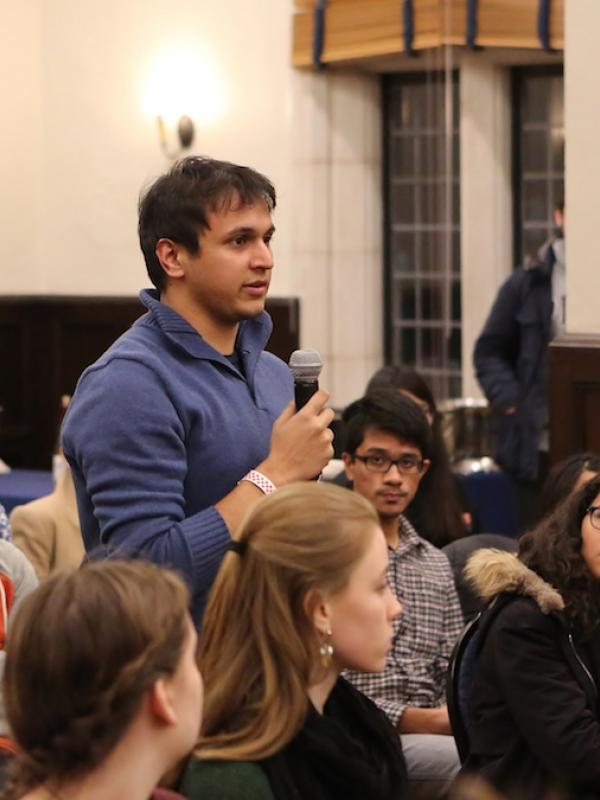 Male student standing with microphone in audience of students