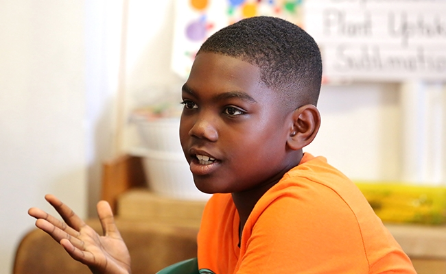 Young boy in orange shirt sitting and talking in classroom