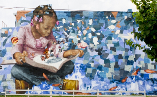 Mural of a young person reading.