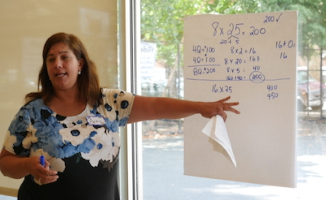 A teacher in the Responsive Math Teaching program points to a poster where she has written out solutions to a multiplication math problem.