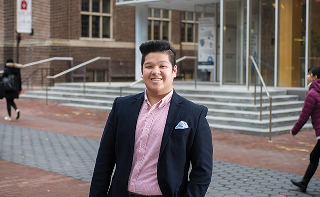 Smiling young man in red-striped shirt and jacket standing outside on Penn's campus.