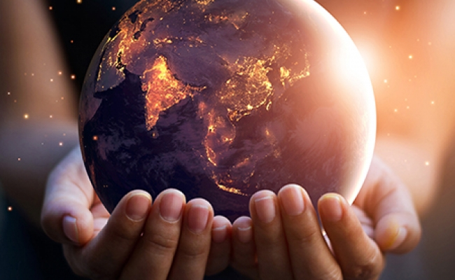 A person holds the planet earth in their cupped hands. The earth is illuminated by city lights and the sun rising on the right side of the planet.