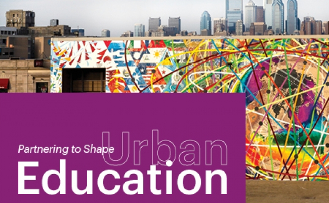 """A colorful mural is painted on a South Philadelphia high school. The Philadelphia skyline is visible behind the school. A purple block in the lower left reads, """"Spring 2020, Partnering to Shape Urban Education"""