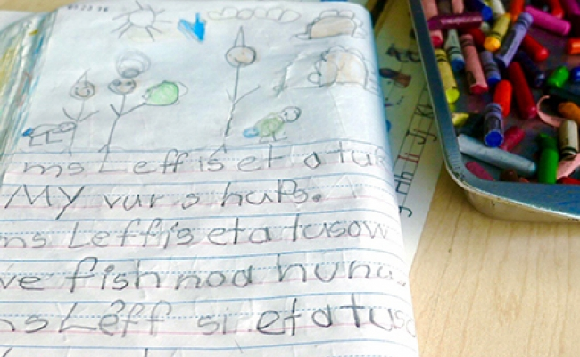 A folded composition book with children's writing and drawings lies next to a tray of crayons