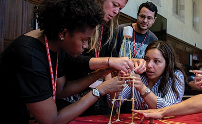 A group of teachers builds a tower from dry spaghetti on a tabletop
