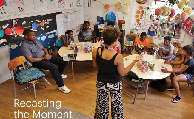 """Elementary school students sit at round tables in a classroom. Behind them are colorful decorations, classroom projects, and school supplies. A woman stands at the front of the room and a man sits to the left. A headline on the image reads, """"Recasting the Moment."""""""