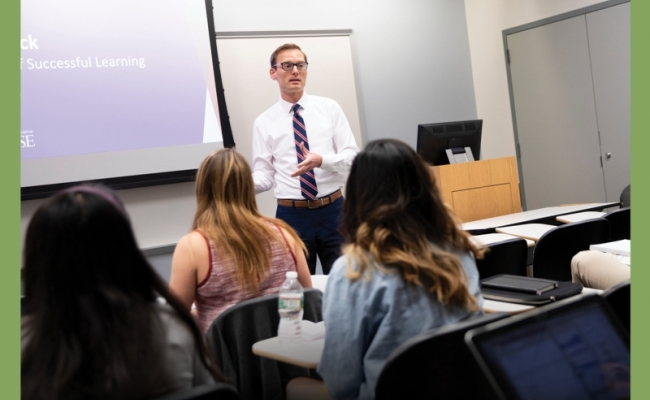 A man wearing glasses and professional attire stands and teaches in front of a classroom.