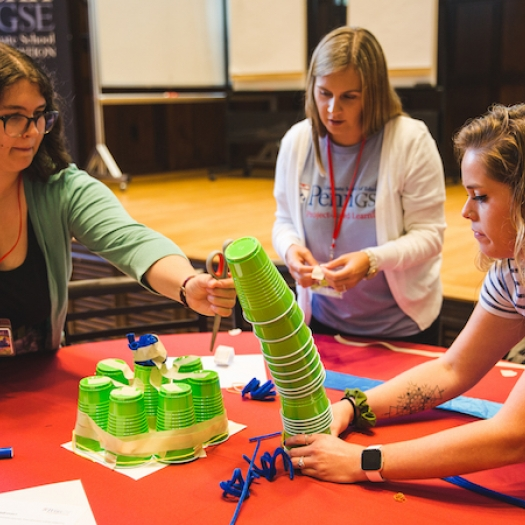 A group of educators attempts to stack cups on a table during a project-based learning professional development workshop.