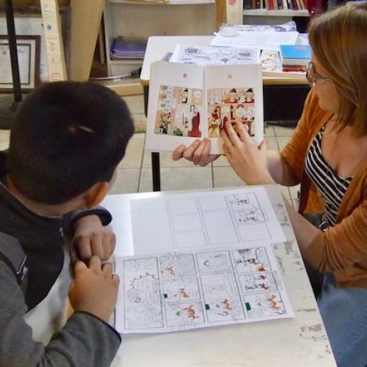 A tutor and a student read a graphic novel together.