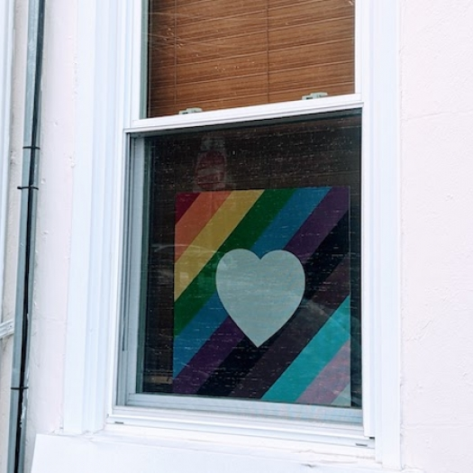 A sign with a heart over a pride flag hangs in the window of a house.
