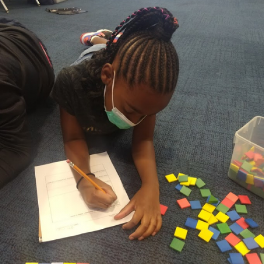 A young student working on the floor