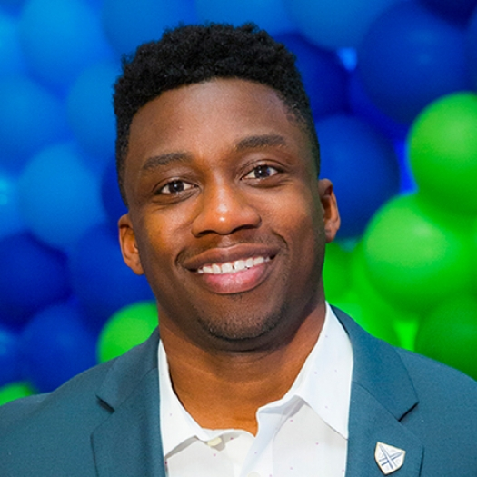 Headshot of a smiling man in a blazer in front of a background of balloons